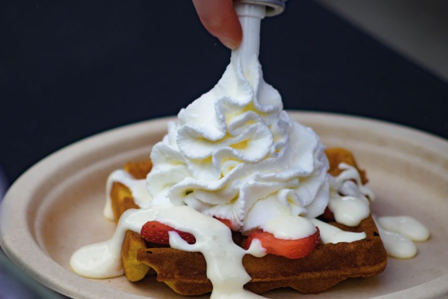 putting whipped cream on a waffle